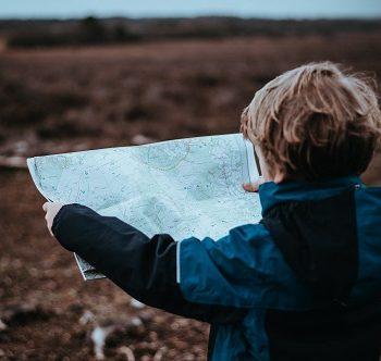 Chłopiec ubrany w kurtkę czytający mapę