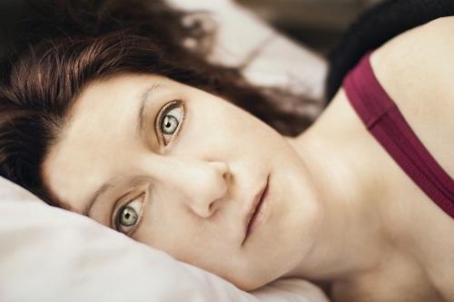 Zatroskana kobieta leży na łóżku