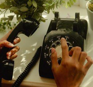 Człowiek wybiera numer na telefonie tarczowym